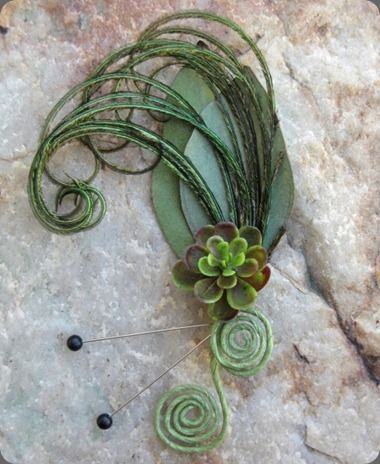 curled peacock feather and succulent bout.   floraldesignbyjac...