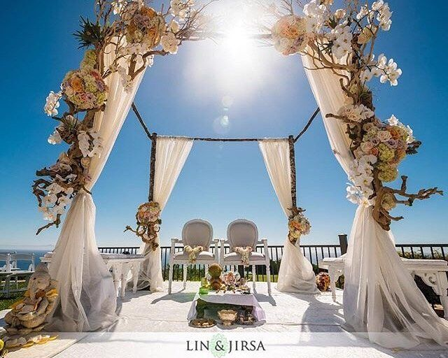 Perfect for brides who want a sweet yet modern outdoor wedding, we just love how this mandap composed of earthy wood branches, pretty rose arrangements, and elegant white draping really showcases a contemporary and sleek design with a slight rustic twist.