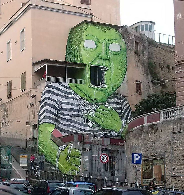 Street artist Blu was recently spotted in Naples, Italy putting the finishing touches on this giant green prisoner tearing free from his uniform. The unannounced artwork is supposedly an allusion to the building it's painted on, a former prison site that is being converted into an open community space. As usual, Blu painted the piece entirely by hand, using ropes to dangle from the side of the building without scaffolding or cherry pickers