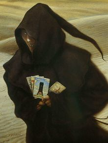 Spooky looking character in a hooded gown, holding fortune cards. The background is a desert.