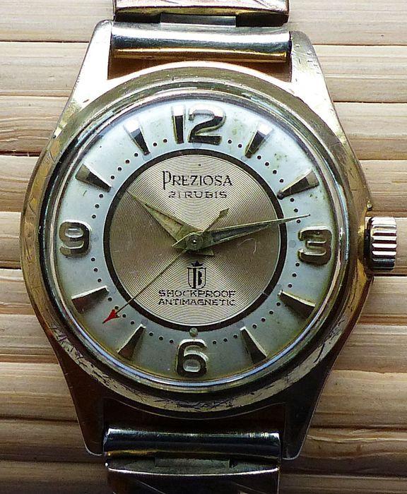 PREZIOSA 21RUBIS - mannen horloge uit de 50s - zeldzame collectible  Fabrikant: Preziosa model met grote centrale tweedeMovement: Mechanical hand-wond met 21RubisMateriaal behuizing: roestvrij staal en goud Doublee 20 Micron 18 K verguldDiameter geval: 32mmArmband materiaal en lengte: RVS Flexarmband 215 mm met inbegrip van de klokLeeftijd van het horloge: 50sStand van de klok is Altersentsprechend goed schuren slijtage en slijtage en kleine krasjes zijn huidige zie foto 'sHet horloge is…