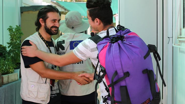 "Syrian lives  Hope – after months of traveling alone    A young refugee says goodbye to an IRC aid worker as he leaves an IRC children's ""Safe Space"" in Greece to be reunited with family in Germany."