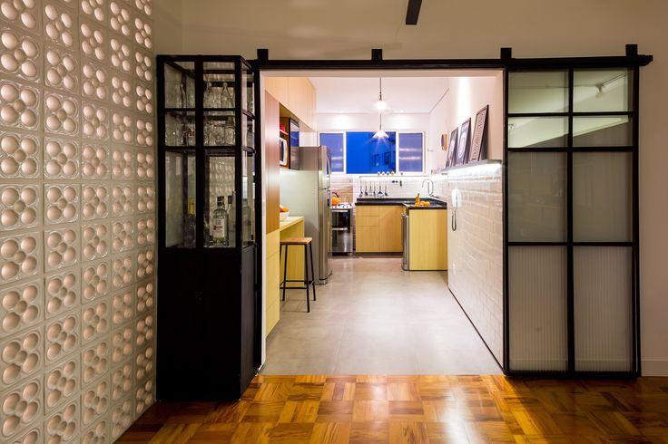 Cozinha com cabamento em madeira, azulejo metro white, serralheria e vidros. Portas metálicas de correr e cristaleira unem o piso de porcelanato cimento queimado com tacos de madeira restaurados.