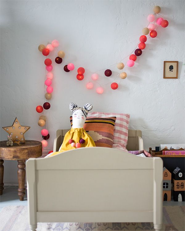 miniature colorful lights draped across the wall and a doll pillow for a cute girl's room
