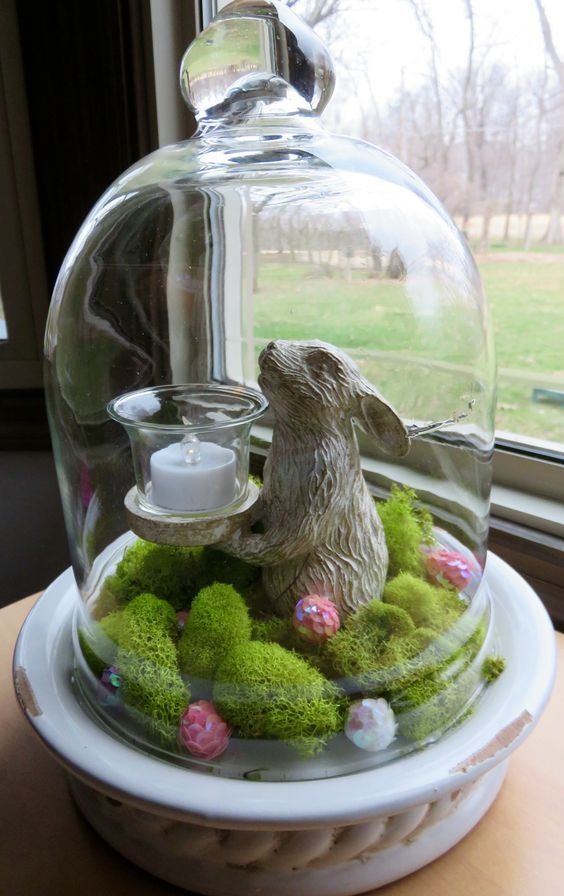 a cloche with a bunny and a candle, moss and sequi…