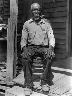 Cudjo Lewis (1841–1935) is considered the last survivor of the last slave ship to enter the United States. He was born around 1841 to a Yoruba family in the Banté region of Dahomey (today Benin). At age 14, he began his training as a soldier & was inducted into oro, the Yoruba secret male society; by age 19, he was undergoing initiation. His initiation training was cut short, however, in the spring of 1860 when soldiers from Dahomey raided his town, killing townspeople & taking prisoners.