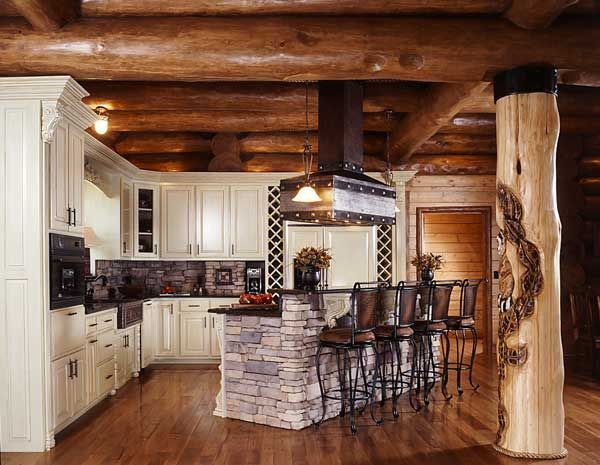 A character post that showcases an owl carving frames the spacious kitchen. The stone-faced island complements the honey-colored hues of the logs. Tyra bought green cabinetry and had coffee-colored stain applied to it to achieve an antique look.