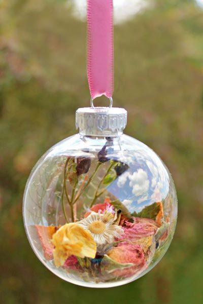 You can also hang your wedding flowers on your Christmas tree. After drying a few of your favorite flowers, simply insert them into a clear glass ball.