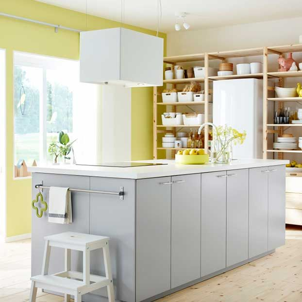 Stunning Kitchen with open wooden shelves a freestanding kitchen block in grey and white and a wall in pastel green by IKEA