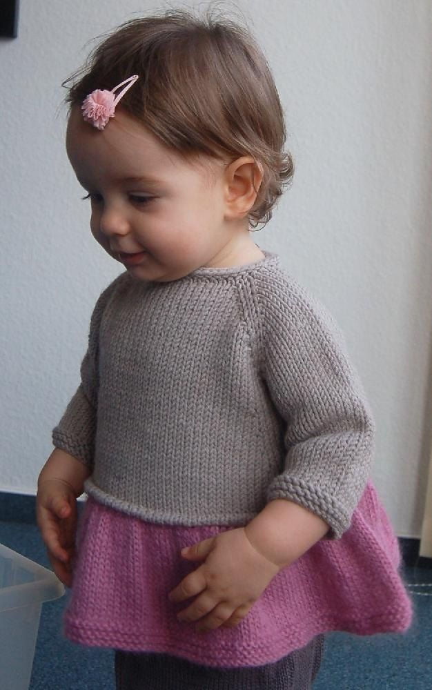 """Sweet and simple and super-swingy… The idea was to give that gauzy, """"tutu"""" feel while keeping this top modern and practical. The result is not too frilly but definitely girly!Knit seamlessly from the top down. First it is worked flat with an I-cord edging, then it is worked in the round. Sts are picked up around the body to create a welt, then the ruffled skirt is worked in the round. Sleeves are worked in the round. An attached I-cord and an I-cord button loop are worked on the neck…"""