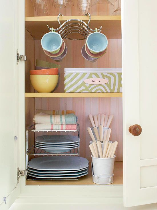 Metal pails and stacked plate storage keep this cabinet organized. See more creative ways to store dishes: http://www.bhg.com/kitchen/storage/organization/creative-ways-to-store-dishes/?socsrc=bhgpin092112metalpailsflatware=3
