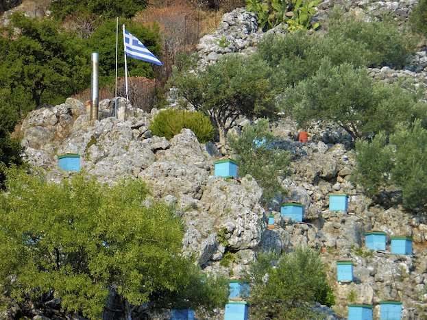 Colourful beehives contrast with the rocky hillside on Cephalonia