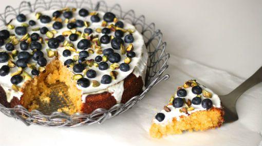 Deze glutenvrije taart met polenta heeft een siroop van limoncello en een glazuur van Griekse yoghurt met blauwe bessen en pistachenoten. Piece of cake!