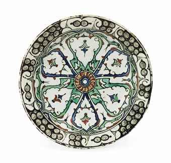 AN IZNIK POTTERY DISH   OTTOMAN TURKEY, CIRCA 1610   With wide sloping rim on short foot, the white interior decorated in cobalt-blue, bole-red, green and black with a central red rosette from which eminate larger palmette petals in alternating green and black filled with stylised floral sprays and framed with split palmettes, within stylised wave and rock border, the exterior with alternating blue and green motifs, intact  12.3in. (31.5cm) diam.