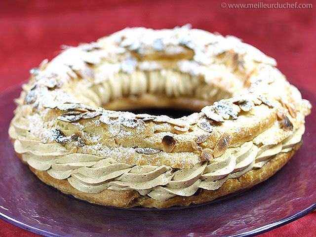Le Paris Brest  Ingrédients :      Pâte à choux :    1/4 litre d'eau    200 g de farine    100 g de beurre    1 pincée de sel    4 œufs entiers      Crème au beurre pralinée :    8 jaunes d'œufs    250 g de sucre    250 g de beurre pommade  praliné      Finition :    100 g d'amandes effilées    50 g de sucre glace    1 jaune d'œuf (dorure)