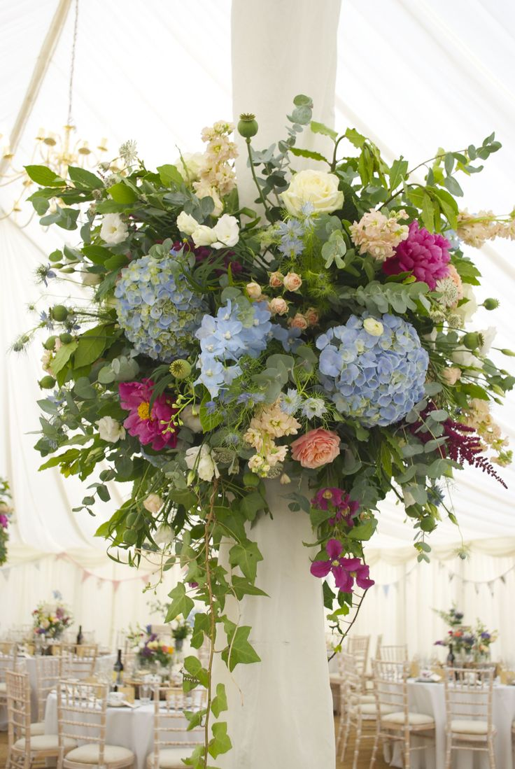 Marquee Pole Flower Balls of pale blue Hydrangea heads, Avalanche Roses, pale blue Delphiniums, pink Clematis, Vuvuzela Roses, and seasonal herbs, designed and created by Hannah Berry Flowers www.hannahberryflowers.co.uk