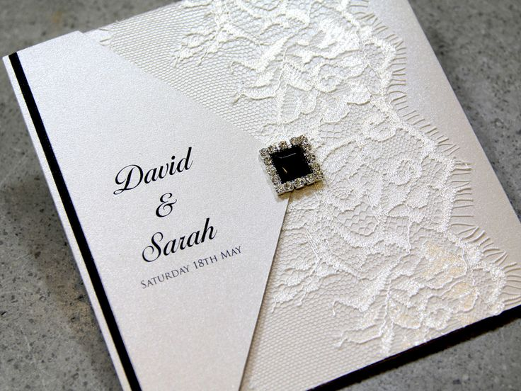 A classic wedding invitation created Chantilly lace and ebony pearl cluster