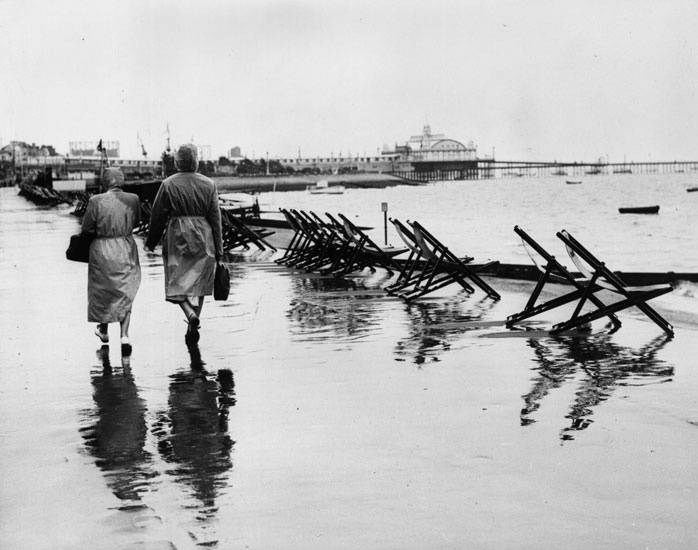 Two women in raincoats walking past a line of empty deckchairs on the promenade at Southend, England, 2nd August 1952. Photo: by William Vanderson/Fox Photos/Getty Images