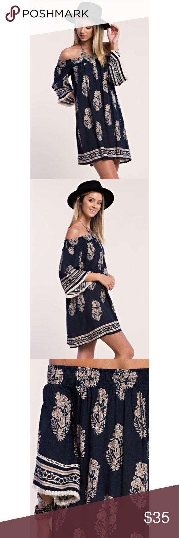 "Boho Beauty Off-Shoulder Dress 🔹Navy with floral/leaf pattern 🔹Off shoulder loose fitting silhouette 🔹Bell sleeves with cream colored tassels 🔹100% Rayon 🔹Length is approx 29"" (measured flat) 🔹Flattering for many body types 🔹Perfect for festival season!  💵Price firm unless bundled 👍🏻Top rated seller 👍🏻Fast shipping 🚫No trades Dresses"