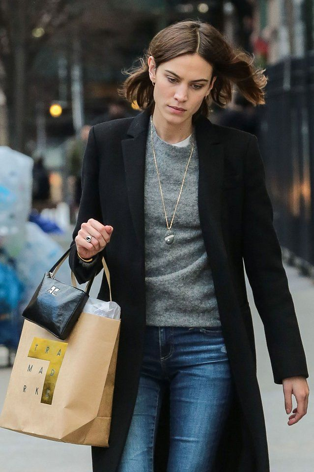 Alexa Chung in a gray sweater, black coat, and jeans