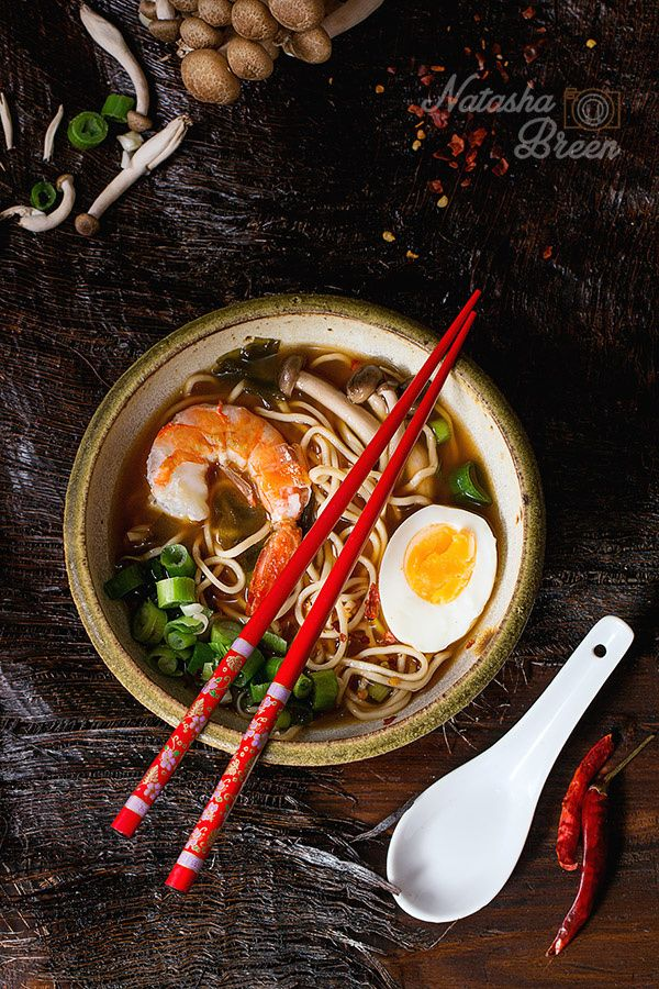Asian Soup with Shrimp - Ceramic bowl of asian ramen soup with shrimp, noodles, spring onion, sliced egg and mushrooms, served with red chopsticks and chili pepper over old wooden table. Dark rustic style. Top view