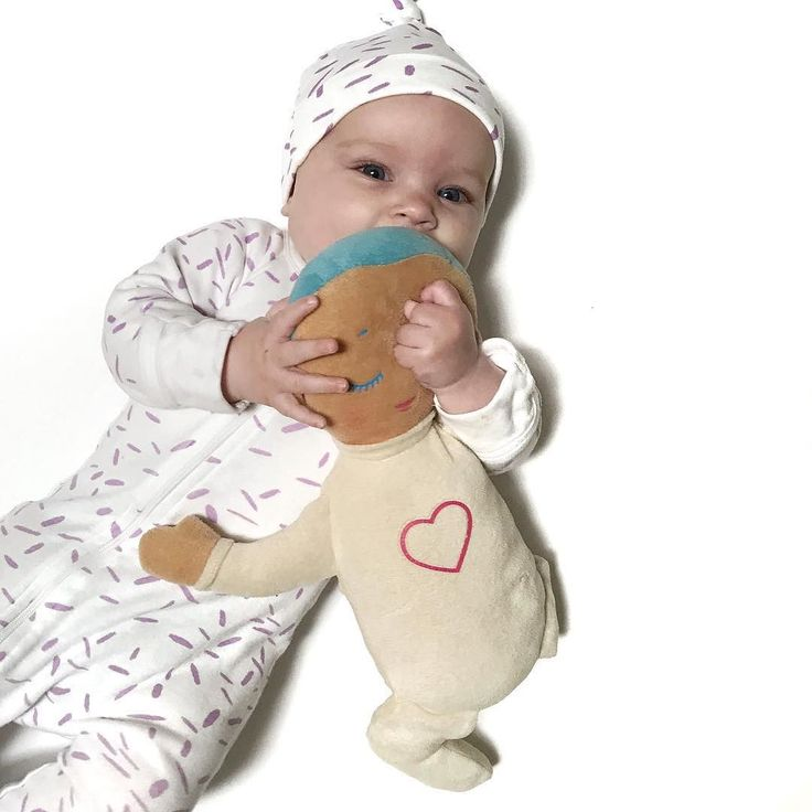 Miss Frankie can't get enough of her Lulla Doll and her @nioviorganics organic outdoor . . . [image is of a white female infant wearing a matching beanie and white romper with lavender spots holding a soft doll called a Lulla Doll against her mouth.]