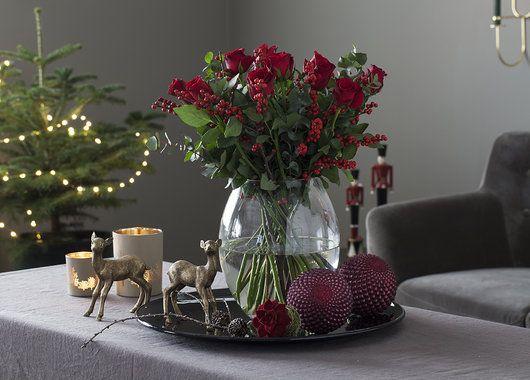 Koselig julestemning med rød julebukett og røde julekuler.