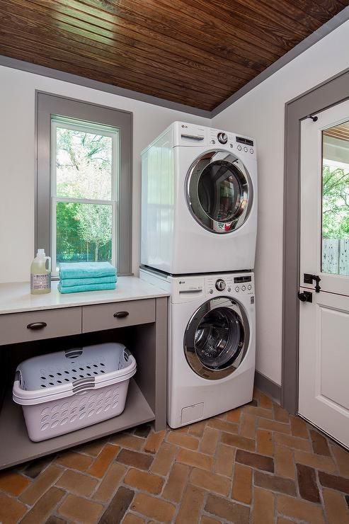Beautiful laundry room marked by its stained plank vaulted ceiling, dutch door, and gray door, window, and crown mouldings features herringbone brick paver flooring and a stacked front loading washer and dryer positioned beside white, plastic laundry bins tucked into a gray laundry folding table fitted with bronze cup pulls and white countertops.