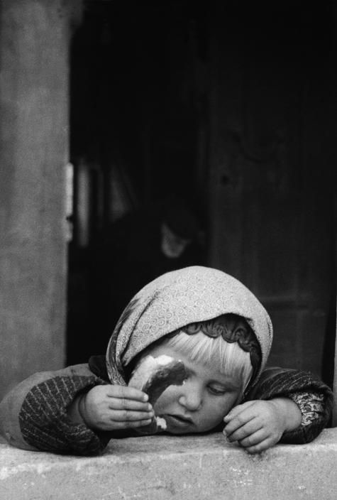 A little girl eating a 'Simit' round piece of bread covered sesame seeds, in the courtyard of a mosque at Unkapani on the Golden Horn, Istanbul. (1956) Photo: Ara Güler