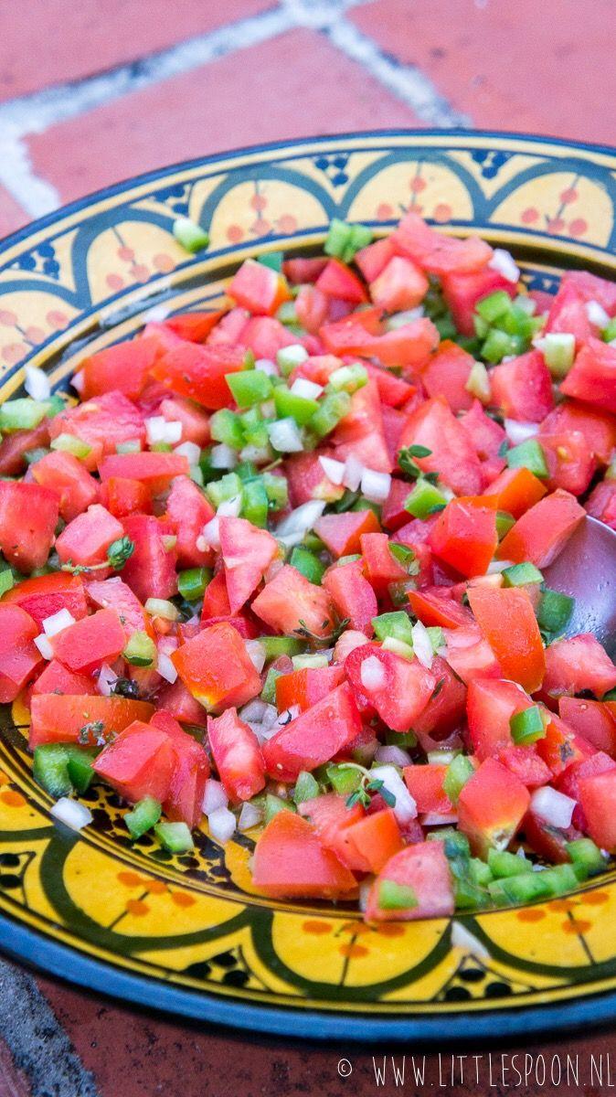 Deze Portugese tomatensalade is goed gevuld met ui, groene paprika en tijm. Heerlijk voor bij de barbecue met een stukje vis of vlees!