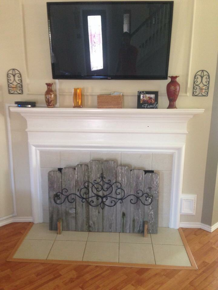 Hide your ugly fireplace behind this easy diy made of weathered fence panels. Screen, cover, whatever you call it. Keep in mind it's made of firewood, so move it far away before you light your fireplace. Lol