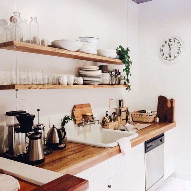 Kitchen with wooden countertop and shelves.