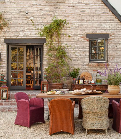 Mismatched woven chairs and a teak table set the scene for meals in the outdoor entertaining area of this California cottage.   - CountryLiving.com