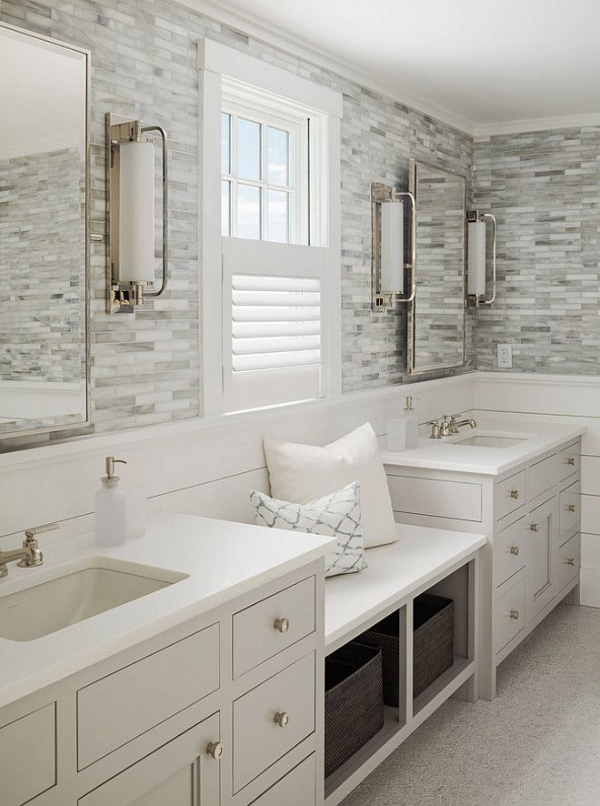 Calming master bathroom with shiplap and tile walls, a window seat flanked by his and her sinks, light gray cabinets and silver hardware | Sophie Metz Design