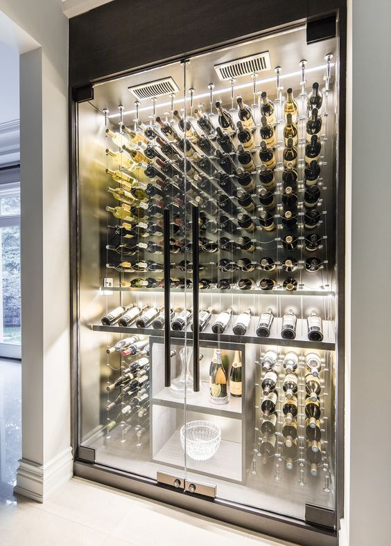Modern custom reach in wine cellar featuring the Cable Wine System…