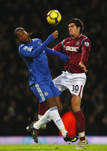 LONDON, ENGLAND - DECEMBER 20:  Didier Drogba of Chelsea is challenged by James Tomkins of West Ham United during the Barclays Premier League match between West Ham United and Chelsea at Upton Park on December 20, 2009 in London, England.  (Photo by Phil Cole/Getty Images)