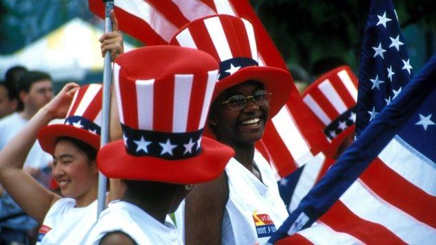 Menschen jubeln mit Stars-and-Stripes-Zylindern und Nationalflaggen - Begeisterung und laute Verurteilung der USA liegen oft dicht beieinander (imago / Siering)