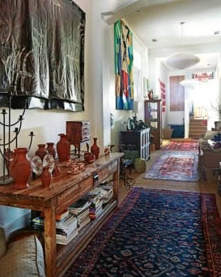 A Fatu Feu'u work hangs above the sideboard, which is one of a matching pair from La Paz, a now-defunct New Plymouth store, and holds terracotta pieces that Paul started collecting when he was a student; the rugs are from Turkey and Afghanistan.