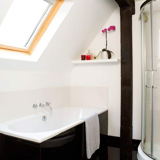 Compact loft bathroom - helpful little shelf, skylight for a view from the bath, and using the corner space for the shower. Source: House to Home