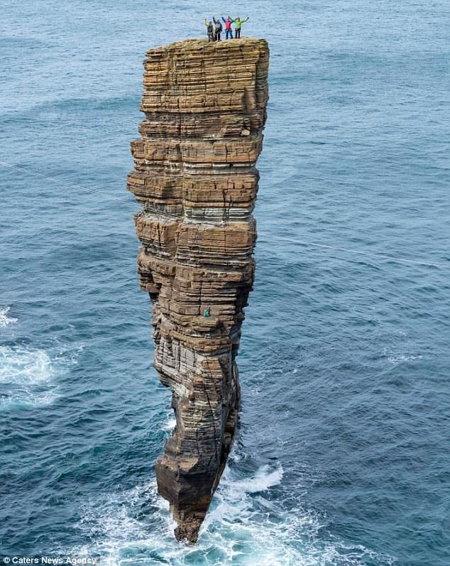 The four daredevils wave as they salute their efforts after climbing to the top of The Castle off Orkney's west coast