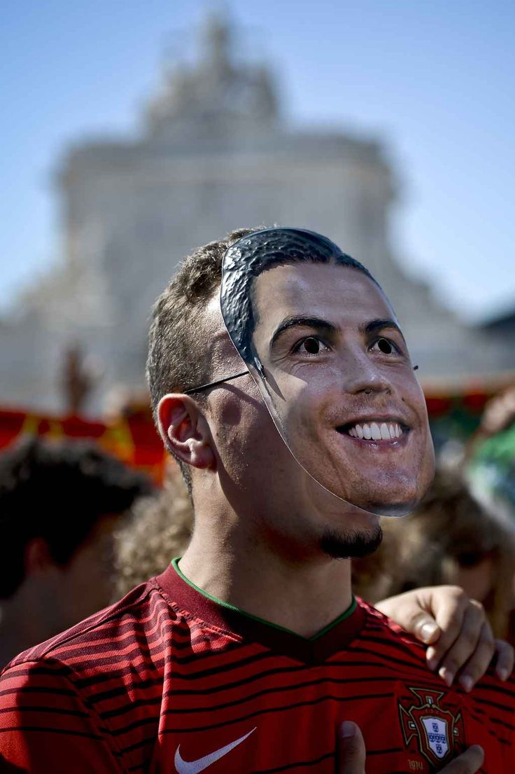 A Portugal football team supporter sporting a mask depicting Portuguese forward Cristiano Ronaldo watches the Euro 2016 group F football match Portugal vs Hungary on a giant screen at Terreiro do Paco square in Lisbon on June 22, 2016. as he watches the Euro 2016 group F football match Portugal vs Hungary on a giant screen at Terreiro do Paco square in Lisbon on June 22, 2016. / AFP PHOTO / PATRICIA DE MELO MOREIRA