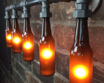 Het licht van de ijdelheid brouwers is een industriële stuk ideaal voor de verlichting van uw bar of de man cave badkamer. De lamp is veelzijdig en werkt als een decoratieve schans of zittend boven uw ijdelheid.  De schans is opgebouwd uit authentieke zwarte ijzeren leidingen. De flessen zijn stevig beveiligd in het zwart ijzer koppeling zonder schade. Een 25 watt lamp wordt gebruikt voor het verlichten van de toevoeging van een warme omgevingslicht bierflesjes.  De onderdelen die worden…