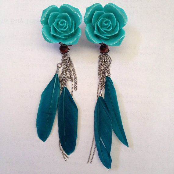 This is a pair of ear plugs / stretchers featuring a turquoise rose on the centre of a silver filigree base with feathers and chain hanging off it. This is attached to a 316L surgical steel tunnels