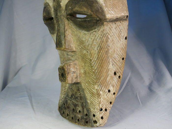 Afrikaanse tribale kunst kifwebe masker, van de Songye etnische groep, gelegen in het oosten van DR Congo. Vintage houten masker met een versleten patina en versierd met kaolien. Het masker geeft goede tekenen van leeftijd, gebruik en blootstelling. Zoals net als andere tribale kunstwerken, ze hebben natuurlijk schaafwonden en slijtage en soms kleine cracks.Approx. 60 jaar oud. Afmetingen: 38 cm. Gewicht: 460 g.