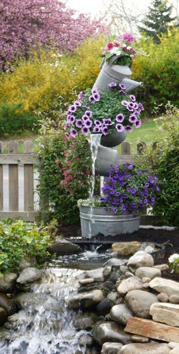 Tipsy galvanized  buckets  and watercan used as a water feature!