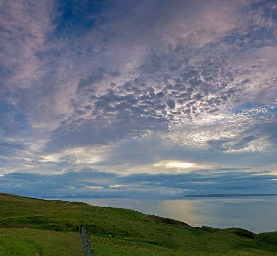 Dawn overlooking the Pentland Firth, Caithness, Scotland, with the Orkney Island of Hoy on the far horizon and Dunnet Head on the near horizon.  Complex layering cloud with cirrostratus and altocumulus stratiformis.