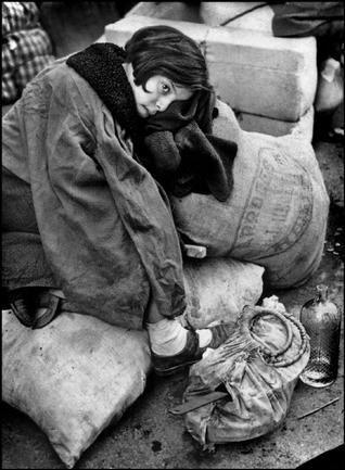 Little girl resting during the evacuation of the city. Barcelona, C/ Aribau 185, January 1939. Photo: Robert Capa.