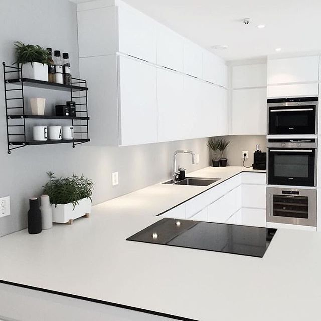 Loving the contrast of the black pocket string shelf in the all white kitchen of @frujosefsen and the living green elements keep the space looking fresh and alive