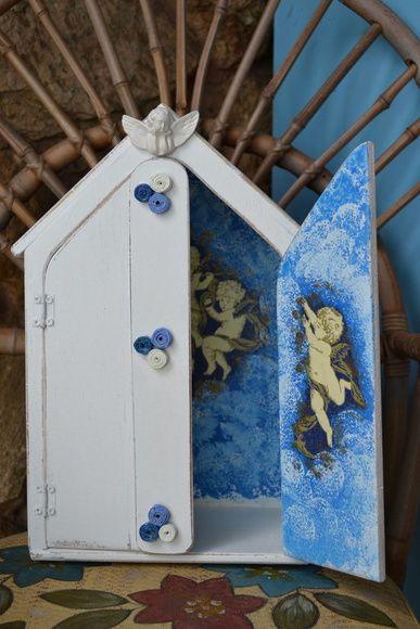 Feito em madeira, pintado em pátina provençal, seu interior é decorado com anjos azuis e seu exterior é decorado com rolinhos de papel nas cores azul claro, azul escuro e gelo. Ideal para quarto de meninos. R$ 55,00