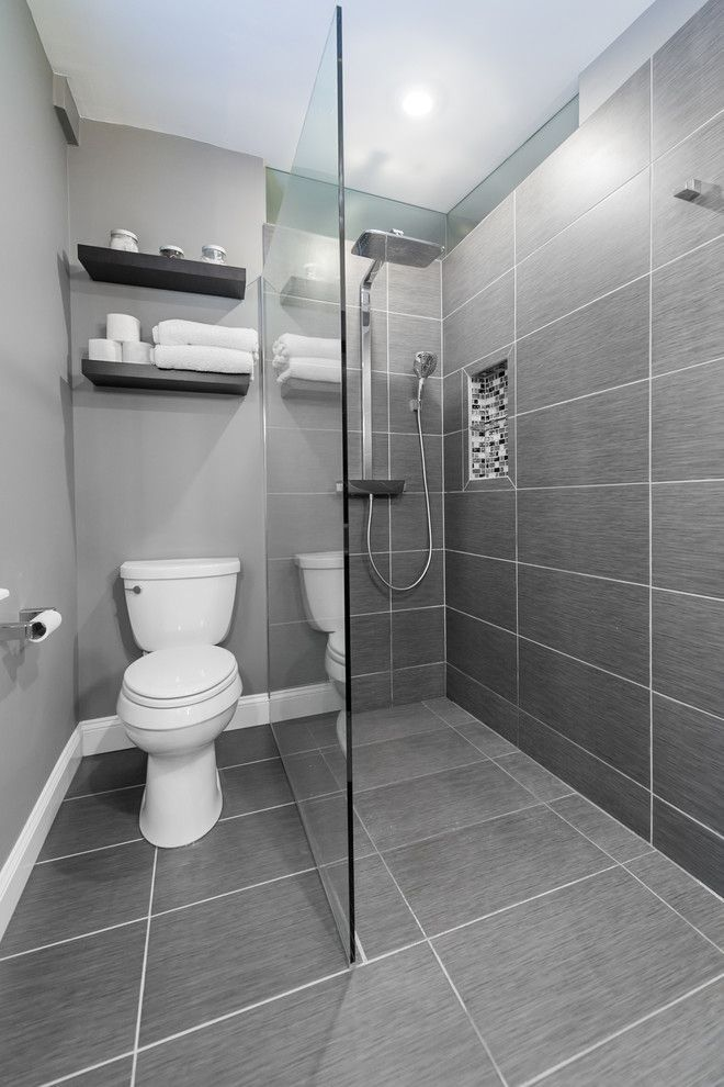 small bathroom with grey flooring, grey tiles in shower wall, grey painted wall in white toilet area, glass panel, wooden shelves on top of the toilet of Small Bathroom with Walk In Shower